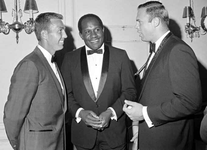 FILE - In this July 9, 1967, file photo, Green Bay Packers' Bart Starr, left, and Willie Davis, center, listen to Chicago Bears' Mike Pyle, right, president of the NFL Players Association, at an awards dinner in Chicago. Willie Davis, a Pro Football Hall of Fame defensive lineman who helped the Green Bay Packers win each of the first two Super Bowls, has died. He was 85. The Packers confirmed Davis' death to the Pro Football Hall of Fame on Wednesday, April 15, 2020. (AP Photo/Charles Harrity, File)
