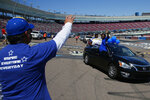 FILE - In this May 16, 2020, file photo Ben Rodriguez, the principal at Buckeye Union High School, waves to graduates during the Parade of Graduates, a drive-thru graduation ceremony, on the race track at Phoenix Raceway in Avondale, Ariz. High schools across the country have added pomp to their circumstances to make graduations special amid the coronavirus pandemic. (AP Photo/Ross D. Franklin, File)