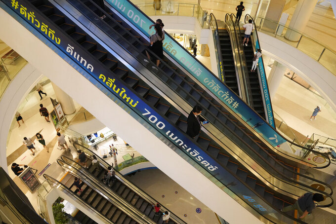 Shoppers ride on an escalator during the opening at the Paragon shopping mall in Bangkok, Thailand, Wednesday, Sept. 1, 2021. Thailand to ease business lockdown measures in the capital and provinces where restrictions have been implemented since mid-July. Malls, hair salons, foot massage parlors, and parks will be allowed to re-open, as well as restaurants for dine-in services but maintained at 50% capacity. (AP Photo/Sakchai Lalit)