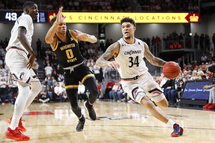 Cincinnati's Jarron Cumberland (34) drives past Wichita State's Dexter Dennis (0) in the second half of an NCAA college basketball game, Sunday, Feb. 17, 2019, in Cincinnati. (AP Photo/John Minchillo)