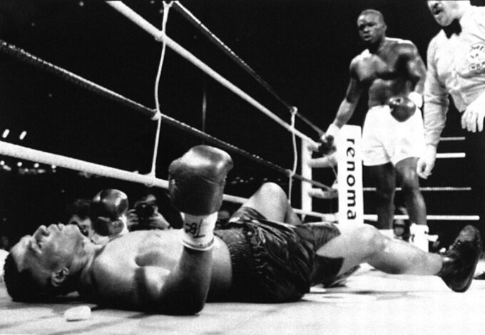"FILE - In this Feb. 11, 1990, file photo, champion Mike Tyson lies flat on his back after being decked by challenger James ""Buster"" Douglas, standing in background, as referee Octavio Meyron keeps counting in the 10th round of the scheduled 12-round heavyweight championship bout at the Tokyo Dome. Douglas is marking the 30th anniversary of his upset boxing victory over Tyson with a campaign aimed to inspiring others who face long odds. The 59-year-old plans to announce the ""42 to 1"" initiative at the Ohio Statehouse Wednesday, Oct. 30, 2019, alongside city and state leaders and two-time Heisman Trophy winner Archie Griffin. The effort will include workforce development, diversity and self-help components.  (Mitsuru Sakai/Kyodo News via AP)"