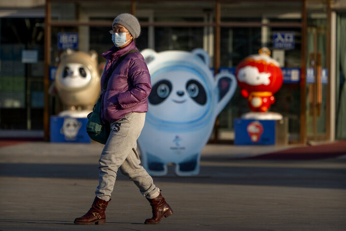 """A woman wearing a face mask to protect against the spread of the coronavirus walks past statues of the 2022 Beijing Winter Olympics and Paralympics mascots on the Olympic Green in Beijing, Tuesday, Feb. 2, 2021. The 2022 Beijing Winter Olympics will open a year from now. Most of the venues have been completed as the Chinese capital becomes the first city to hold both the Winter and Summer Olympics. Beijing held the 2008 Summer Olympics. But these Olympics are presenting some major problems. They are already scarred by accusations of rights abuses including """"genocide""""against more than 1 million Uighurs and other Muslim ethnic groups in western China. (AP Photo/Mark Schiefelbein)"""