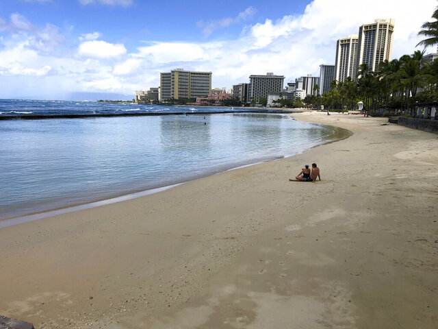 FILE - In this March 28, 2020, file photo, a couple sits on an empty section of Waikiki Beach in Honolulu. Hawaii law enforcement authorities are cracking down on rogue tourists who are visiting beaches, jetskiing, shopping and generally flouting strict requirements that they quarantine for 14 days after arriving.   (AP Photo/Caleb Jones, File)