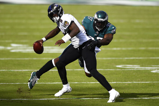 Baltimore Ravens' Lamar Jackson (8) tries to get free from Philadelphia Eagles' Malik Jackson (97) plays during the second half of an NFL football game, Sunday, Oct. 18, 2020, in Philadelphia. (AP Photo/Derik Hamilton)