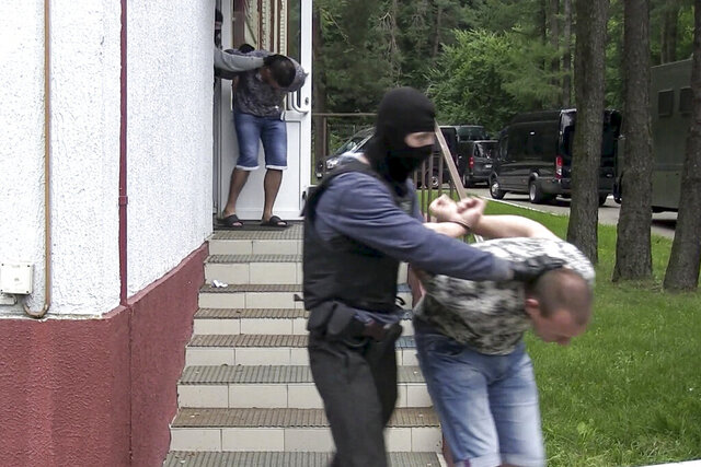 In this photo taken from video released by Belarusian KGB, State TV and Radio Company of Belarus on Wednesday, July 29, 2020, Belarusian KGB officers detain Russian men in a sanitarium outside in Minsk, Belarus. Belarusian officials said that more than 30 detained employees of private Russian military contractor Wagner are facing a criminal probe on charges of plotting terror attacks in Belarus amid a presidential election campaign. (Belarusian KGB, State TV and Radio Company of Belarus via AP)