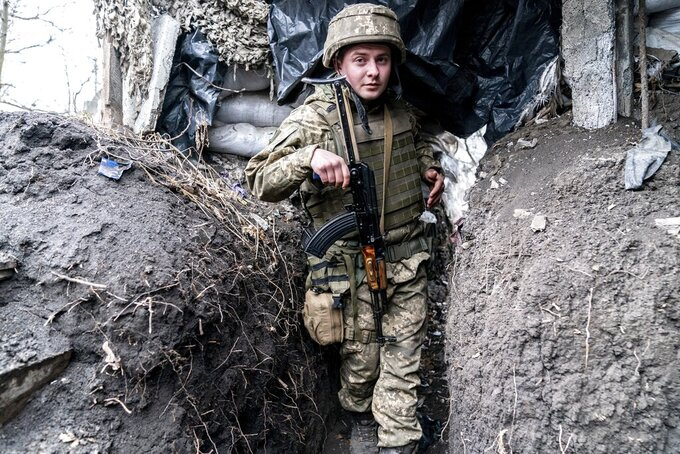 """Ukrainian serviceman Serhiy Kochuk walks along a trench near the front-line town of Krasnohorivka, eastern Ukraine, Friday, March 5, 2021. In the front-line town of Krasnohorivka, soldiers widely refuse to vaccinate. """"I have little faith in a pandemic, I don't think it's some kind of serious disease,"""" said Serhiy Kochuk, a 25-year-old soldier who has been on duty at the front line. """"I am healthy, but the vaccine can provoke illness; because of this vaccine you can get sick."""" (AP Photo/Evgeniy Maloletka)"""