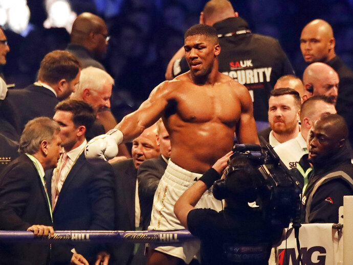 FILE- In this file photo dated Saturday, April 29, 2017, British boxer Anthony Joshua celebrates after beating Ukrainian Wladimir Klitschko at Wembley stadium in London.  Big punching contenders Anthony Joshua and Joseph Parker will put their titles and reputations on the line it is announced Sunday Jan. 14, 2018, when they meet for a world heavyweight title clash in Cardiff on upcoming March 31. (AP Photo/Matt Dunham, FILE)