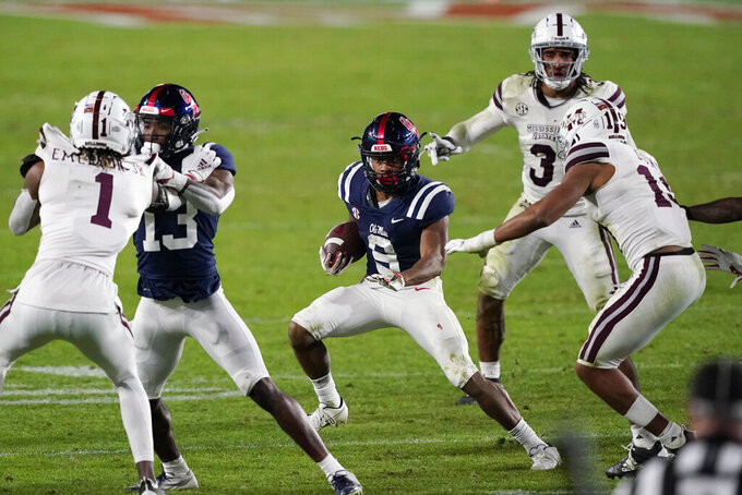 Mississippi running back Jerrion Ealy (9) looks for running room as Mississippi State defenders pursue during the second half of an NCAA college football game Saturday, Nov. 28, 2020, in Oxford, Miss. Mississippi won 31-24. (AP Photo/Rogelio V. Solis)