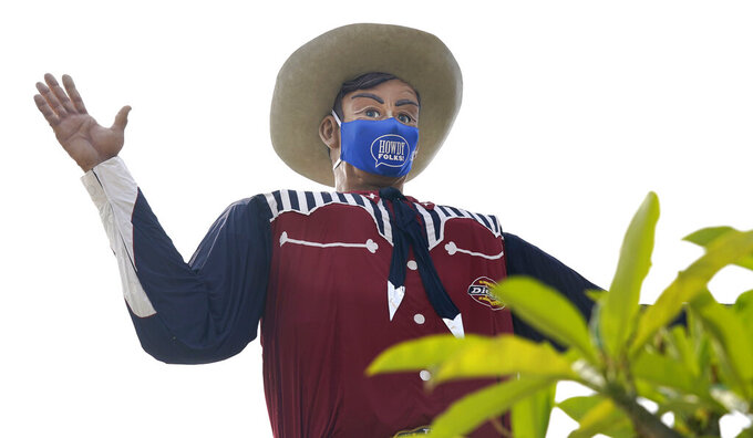 The famous giant Big Tex wears a mask at Fair Park in Dallas on Sept. 19, 2020. The Texas-Oklahoma college football matchup will be a different game-day atmosphere this year with small crowds, no State Fair, a few food vendors, masks and social distancing. (AP Photo/LM Otero