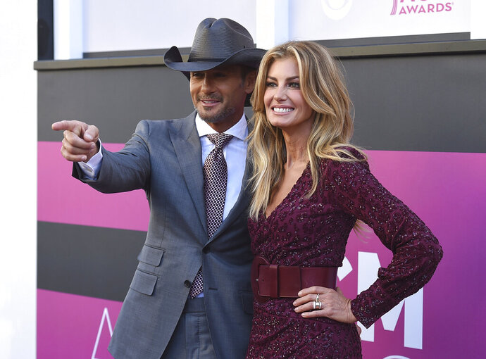 """FILE - In this Sunday, April 2, 2017, file photo, Tim McGraw, left, and Faith Hill arrive at the 52nd annual Academy of Country Music Awards at the T-Mobile Arena in Las Vegas. The government's small business lending program has benefited millions of companies, with the goal of minimizing the number of layoffs Americans have suffered in the face of the coronavirus pandemic. Yet the recipients include many you probably wouldn't have expected. A Nashville, Tenn., company called """"Road Dog Touring, Inc."""" was approved for a small business loan of $2 million to $5 million. The company owns the official website for country singer Tim McGraw, timmccgraw.com, and a joint official site with his wife, Faith Hill, timandfaith.com. (Photo by Jordan Strauss/Invision/AP, File)"""
