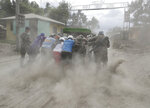 Police and military help push a vehicle along a road covered in volcanic ash at a village beside Taal volcano where residents have evacuated to safer ground in Agoncillo, Batangas province, southern Philippines on Saturday Jan. 18, 2020. The Taal volcano near the Philippine capital emitted more ash clouds Saturday, posing the threat of another eruption. (AP Photo/Aaron Favila)