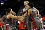 Utah guard Parker Van Dyke, second from right, is mobbed by teammates after making a three-point basket to win an NCAA college basketball game against UCLA, Saturday, Feb. 9, 2019, in Los Angeles. (AP Photo/Marcio Jose Sanchez)