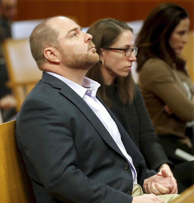 This photo taken Jan. 28 2020, shows John Cox, left, a pediatric doctor formerly at Children's Hospital of Wisconsin, sitting with his wife, Sadie Dobrozsi, also a doctor, before Cox appears in a Milwaukee County court in Milwaukee. A judge on Wednesday, Feb. 12, 2020, declined to dismiss a complaint charging Cox with physically injuring an infant he was adopting with his wife.(Mike De Sisti/Milwaukee Journal-Sentinel via AP)