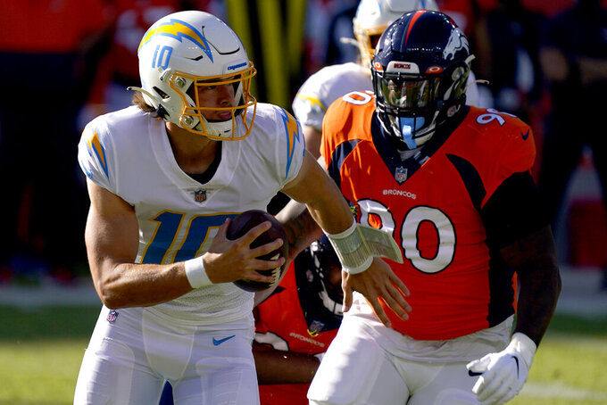 Los Angeles Chargers quarterback Justin Herbert (10) runs the ball during the first half of an NFL football game as Denver Broncos defensive end DeShawn Williams (90) pursues, Sunday, Nov. 1, 2020, in Denver. (AP Photo/David Zalubowski)