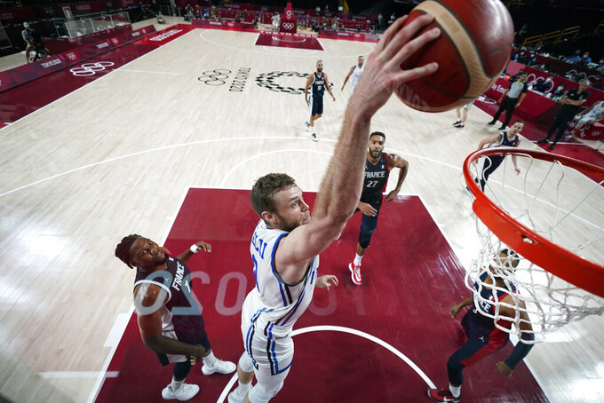 Italy's Nicolo Melli dunks the ball ahead of France's Guerschon Yabusele, left, during a men's basketball quarterfinal round game at the 2020 Summer Olympics, Tuesday, Aug. 3, 2021, in Saitama, Japan. (AP Photo/Charlie Neibergall, Pool)