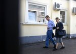 FILE - In this file photo taken on July 26, 2019, opposition candidate and lawyer at the Foundation for Fighting Corruption, Lyubov Sobol leaves the Russian Investigative Committee with her lawyer after been summoned for questioning, in Moscow, Russia.  Sobol, who was on a hunger strike for a month protesting an official refusal to register her to run for the Moscow city legislature, argues that the Kremlin won't be able to stop the rising wave of public discontent as more and more Russians are losing trust in authorities. (AP Photo/Pavel Golovkin, File)