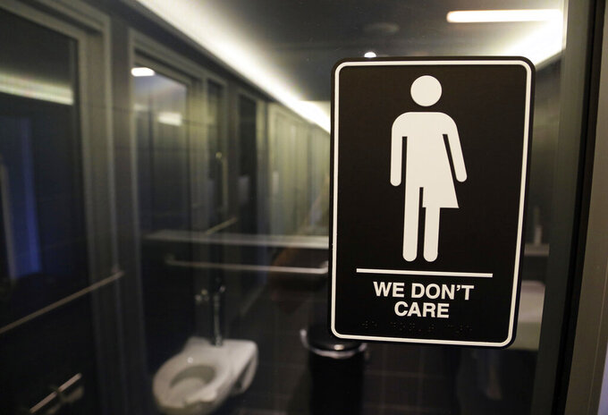 "FILE - In this May 12, 2016, file photo, gender free sign hangs outside a restroom at 21c Museum Hotel in Durham, N.C. A 3 1/2-year ban on local ordinances aimed at protecting LGBT rights in North Carolina expired Tuesday, Dec. 1, 2020, prompting gay rights groups to urge the passage of such measures. Democratic Gov. Roy Cooper agreed to the moratorium in March 2017 in exchange for GOP lawmakers agreeing to do away with portions of a ""Bathroom Bill"" that Republicans had approved a year earlier.(AP Photo/Gerry Broome, File)"