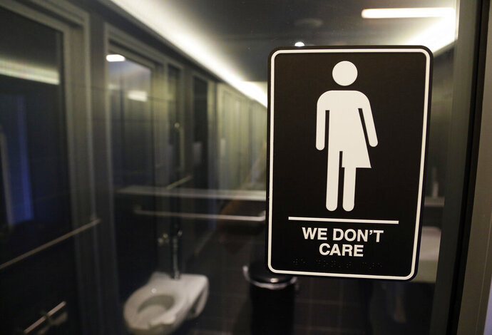 """FILE - In this May 12, 2016, file photo, gender free sign hangs outside a restroom at 21c Museum Hotel in Durham, N.C. A 3 1/2-year ban on local ordinances aimed at protecting LGBT rights in North Carolina expired Tuesday, Dec. 1, 2020, prompting gay rights groups to urge the passage of such measures. Democratic Gov. Roy Cooper agreed to the moratorium in March 2017 in exchange for GOP lawmakers agreeing to do away with portions of a """"Bathroom Bill"""" that Republicans had approved a year earlier.(AP Photo/Gerry Broome, File)"""
