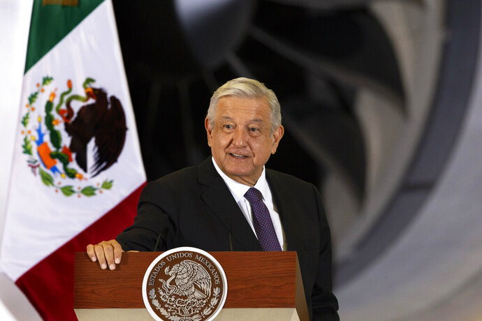 FILE - In this July 27, 2020 file photo, Mexican President Andres Manuel Lopez Obrador gives his daily, morning press conference in front of the former presidential plane that has been for sale since he took office, at Benito Juarez International Airport in Mexico City. López Obrador said Tuesday, Sept. 15, 2020 he will ask the Senate to schedule a referendum on whether to investigate and possibly bring charges against his predecessors, including almost all of Mexico's living ex-presidents. (AP Photo/Marco Ugarte, File)