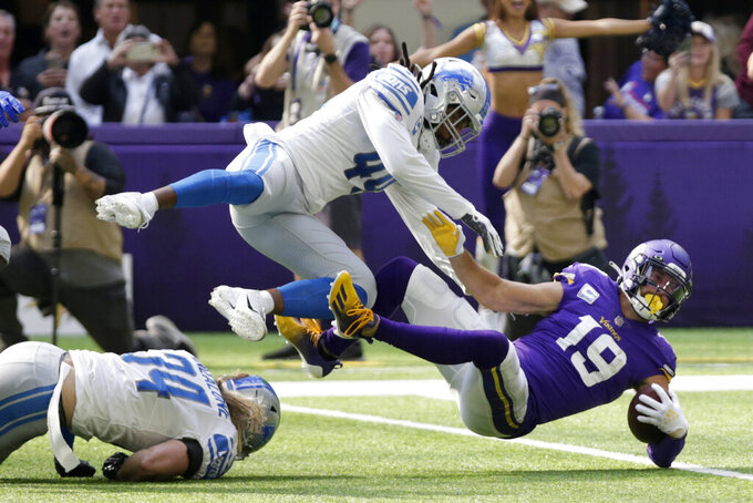 Minnesota Vikings wide receiver Adam Thielen (19) is tackled by Detroit Lions linebacker Jalen Reeves-Maybin (44) after catching a pass during the first half of an NFL football game, Sunday, Oct. 10, 2021, in Minneapolis. (AP Photo/Andy Clayton-King)
