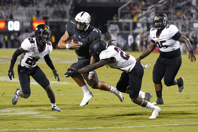 Central Florida quarterback Joey Gatewood (7) carries as Bethune-Cookman cornerback Henry Miller II (28), cornerback Devuntray Hampton, center, and defensive lineman Reginald Pearson, right, defend during the second half of an NCAA college football game Saturday, Sept. 11, 2021, in Orlando, Fla. (AP Photo/John Raoux)