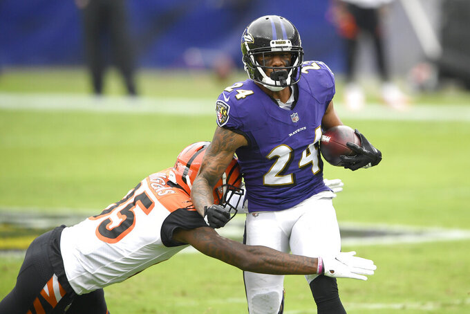 Cincinnati Bengals wide receiver Tee Higgins, left, makes a tackle on Baltimore Ravens cornerback Marcus Peters after he intercepted a pass from Bengals quarterback Joe Burrow during the first half of an NFL football game, Sunday, Oct. 11, 2020, in Baltimore. (AP Photo/Nick Wass)