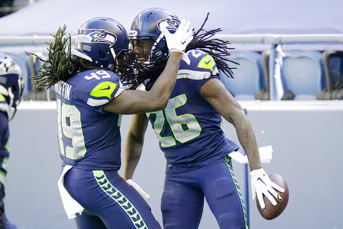 Seattle Seahawks cornerback Shaquill Griffin (26) is greeted by his twin brother, outside linebacker Shaquem Griffin (49) after Shaquill Griffin intercepted a pass against the Dallas Cowboys during the first half of an NFL football game, Sunday, Sept. 27, 2020, in Seattle. (AP Photo/Elaine Thompson)