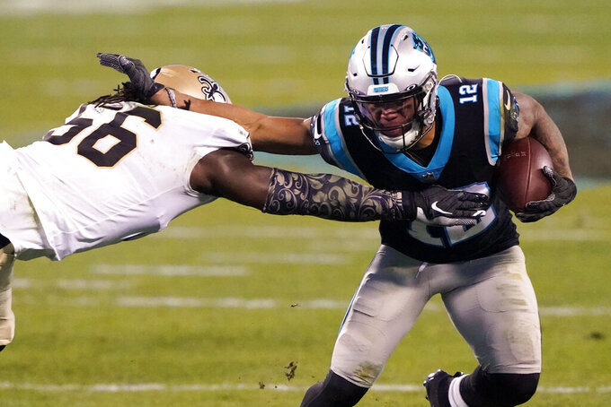 Carolina Panthers wide receiver D.J. Moore, right, runs around New Orleans Saints outside linebacker Demario Davis during the first half of an NFL football game Sunday, Jan. 3, 2021, in Charlotte, N.C. (AP Photo/Brian Blanco)