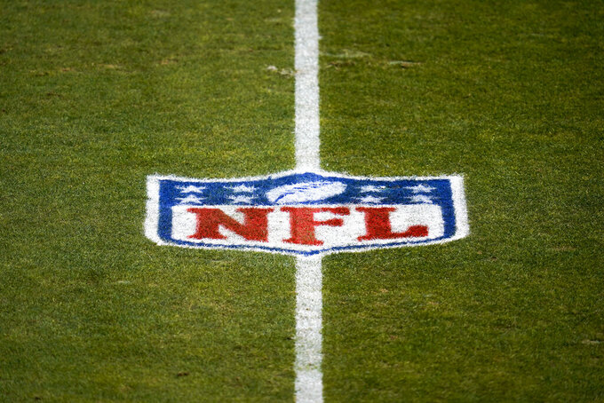 File-This Jan. 3, 2021, file photo shows the NFL logo on the field before a game between the Denver Broncos and the Las Vegas Raiders in Denver. The NFL and NFL Players Association have updated COVID-19 protocols to loosen restrictions for fully vaccinated players and to encourage others to get the vaccine. Unvaccinated players must continue to get daily testing, wear masks and practice physical distancing. They won't be allowed to eat meals with teammates, can't participate in media or marketing activities while traveling, aren't permitted to use the sauna or steam room and may not leave the team hotel or interact with people outside the team while traveling. (AP Photo/Jack Dempsey, File)
