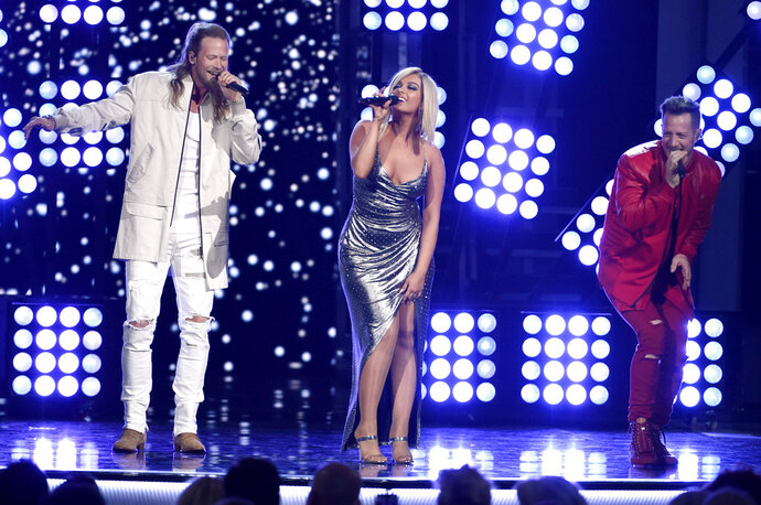 FILE - In this April 15, 2018 file photo, Tyler Hubbard, right, and Brian Kelley, left, of Florida Georgia Line, and Bebe Rexha, center, perform