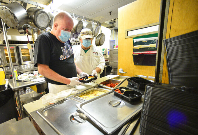 Ray Bronson and Dean Lafayette, left to right, chefs at Brattleboro Senior Meals, in Brattleboro, Vt., prepare a dish that will be delivered to residents in the community on Thursday, May 21, 2020. (Kristopher Radder/The Brattleboro Reformer via AP)