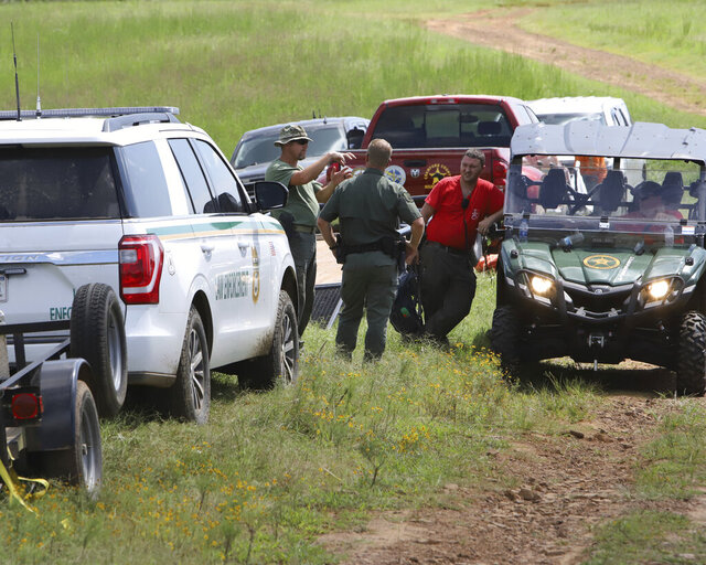 U.S. Forest Service and Crawford County Sheriff Department personnel gather in Chester, Ark., Saturday, Sept. 5, 2020, near the site of a plane crash. Authorities say four members of a family from Oklahoma were killed when their single-engine plane crashed into a ravine Friday evening, Sept. 4 in rural northwest Arkansas.  (Jamie Mitchell/Southwest Times Record via AP)