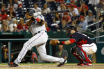 Miami Marlins' Starlin Castro, left, singles in front of Washington Nationals catcher Yan Gomes in the eighth inning of a baseball game, Friday, May 24, 2019, in Washington. Curtis Granderson scored on the play. (AP Photo/Patrick Semansky)