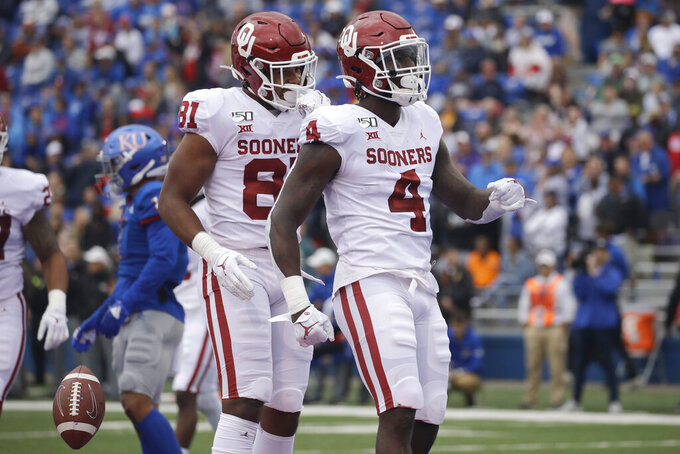 Oklahoma running back Trey Sermon (4) celebrates in the end zone after scoring a touchdown during the first half of an NCAA college football game against Kansas, Saturday, Oct. 5, 2019, in Lawrence, Kan. (AP Photo/Charlie Riedel)