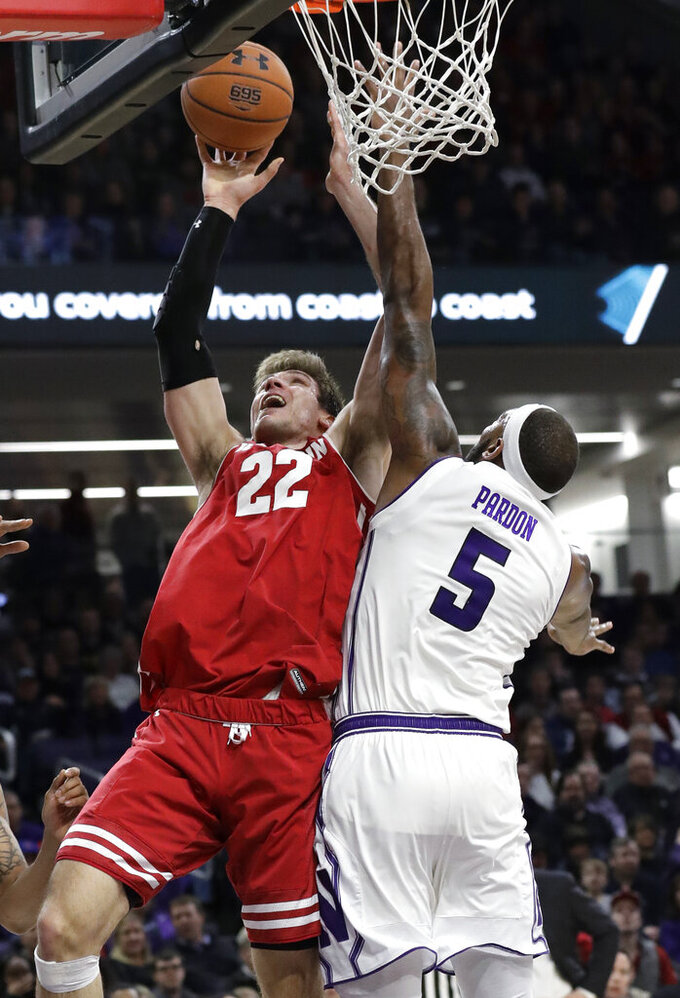 Wisconsin forward Ethan Happ, left, shoots against Northwestern center Dererk Pardon during the first half of an NCAA college basketball game Saturday, Feb. 23, 2019, in Evanston, Ill. (AP Photo/Nam Y. Huh)