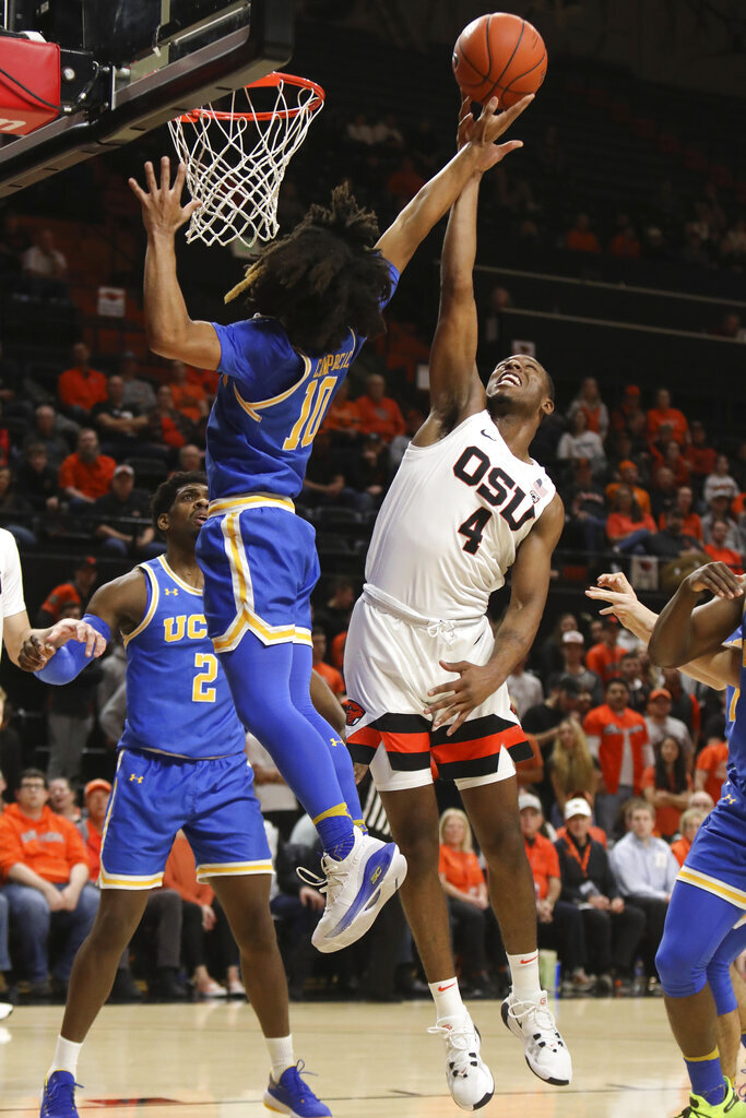 UCLA's Tyger Campbell (10) blocks a basket by Oregon State's Alfred Hollins (4) during the first half of an NCAA college basketball game in Corvallis, Ore., Thursday, Jan. 23, 2020. (AP Photo/Amanda Loman)