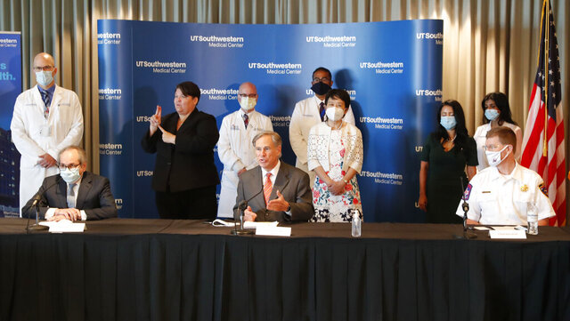 Texas Gov. Greg Abbott, center, speaks during a news conference in Dallas, Thursday, Aug. 6, 2020. UT Southwestern Medical Center hosted a round table discussion about preparations for the upcoming flu season amid the ongoing coronavirus pandemic. (AP Photo/LM Otero)