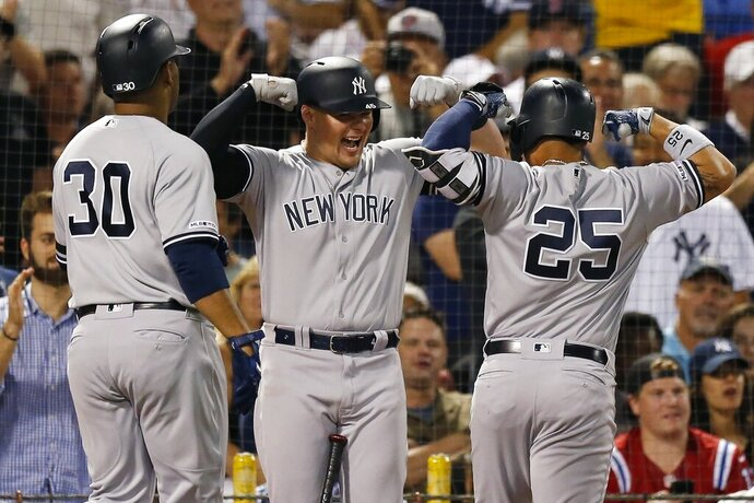 New York Yankees' Gleyber Torres (25) celebrates his two-run home with Luke Voit, center, that also drove in Edwin Encarnacion during the second inning of a baseball game against the Boston Red Sox in Boston, Sunday, Sept. 8, 2019. (AP Photo/Michael Dwyer)
