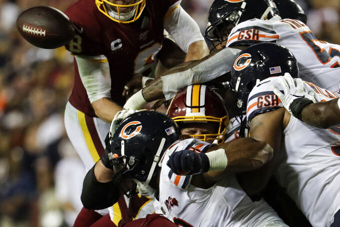 Washington Redskins quarterback Case Keenum, center, fumbles the ball as he is hit by several of the Chicago Bears defenders during the second half of an NFL football game Monday, Sept. 23, 2019, in Landover, Md. (AP Photo/Julio Cortez)