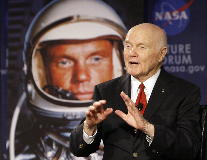 FILE - In this Feb. 20, 2012, file photo, U.S. Sen. John Glenn talks with astronauts on the International Space Station via satellite in Columbus, Ohio. Retired astronaut Mark Kelly entered the race Tuesday, Feb. 12, 2019 to finish John McCain's term in the U.S. Senate, looking to join a small club of astronauts who have traded an office in outer space for the U.S. Capitol. The first American to orbit the Earth, Glenn was later elected to the U.S. Senate from Ohio and served four terms. (AP Photo/Jay LaPrete, File)