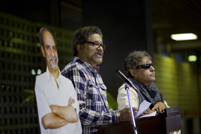FILE - In this Sept. 23, 2014 file photo, Luciano Marin, alias Iván Marquez, chief negotiator for the Revolutionary Armed Forces of Colombia, FARC, flanked by a life-size cut out image of rebel commander Jaime Palmera, alias