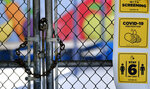 A chain-link fence lock is seen on a gate at a closed Ranchito Elementary School in the San Fernando Valley section of Los Angeles on Monday, July 13, 2020. Amid spiking coronavirus cases, Los Angeles Unified School District campuses will remain closed when classes resume in August, Superintendent Austin Beutner said Monday. (AP Photo/Richard Vogel)