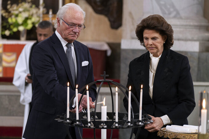 Sweden's King Carl Gustaf and Queen Silvia light candles during a Memorial service at Drottningholm Palace Church in Stockholm, Thursday, March 11, 2021. Sweden's King Carl XVI Gustaf and his wife Queen Silvia held a church ceremony on Thursday to honour the victims of the coronavirus, on the one-year anniversary of the first death of the pandemic in the Scandinavian nation. The royal couple participated, but Crown Princess Victoria and Prince Daniel could not attend as they both tested positive for covid-19 earlier in the day. (Jonas Borg/Royal Court of Sweden via AP)