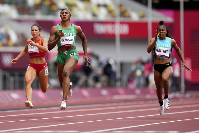 FILE - In this July 30, 2021 file photo, Blessing Okagbare, of Nigeria, center, wins a heat in the women's 100-meter run at the 2020 Summer Olympics, in Tokyo. Nigerian sprinter Okagbare is facing three charges in a doping case which surfaced in dramatic circumstances when she was barred from running in the Olympic 100-meter semifinals hours before the race. The Athletics Integrity Unit revealed on Thursday, Oct. 7, 2021, that Okagbare tested positive for blood booster EPO in Nigeria in June, in addition to another failed test for human growth hormone in Slovakia in July, which was announced during the Olympics. (AP Photo/Petr David Josek, file)