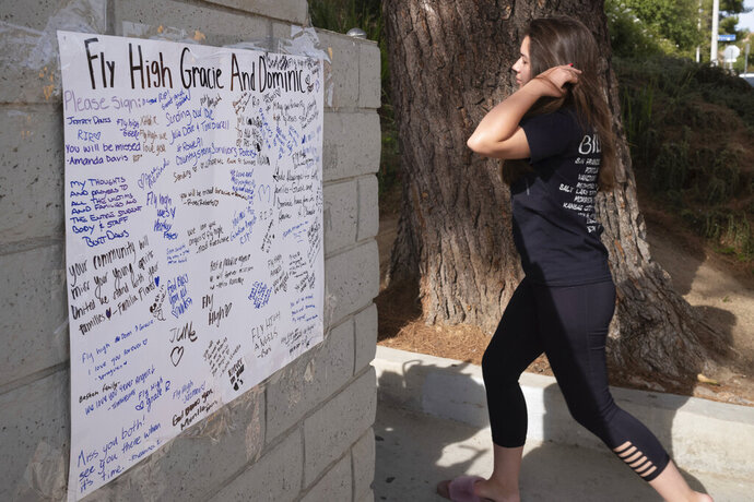 Saugus high students walk past a memorial with well wishes placed up for Gracie Muehlberger and Dominic Blackwell Tuesday, Nov. 19, 2019. Students were allowed back to collect their belongings left behind after the tragic shooting last Thursday. Classes will resume at the high school on Dec. 2. (David Crane/The Orange County Register via AP)