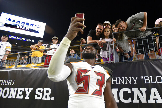 Tampa Bay Buccaneers linebacker Demone Harris takes a selfie with fans following the team's NFL preseason football game against the Pittsburgh Steelers in Pittsburgh, Friday, Aug. 9, 2019. The Steelers won 30-28. (AP Photo/Don Wright)