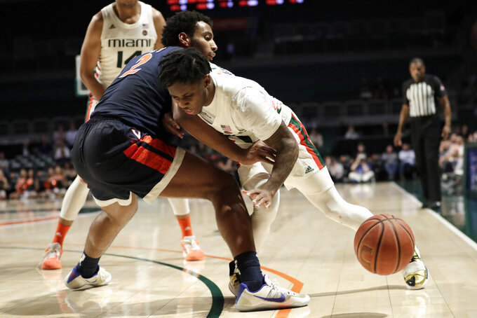 Miami guard Chris Lykes, right, loses the ball as Virginia guard Braxton Key (2) defends during the second half of an NCAA college basketball game, Wednesday, March 4, 2020, in Coral Gables, Fla. Virginia won 46-44. (AP Photo/Lynne Sladky)