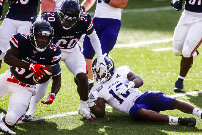 Western Carolina running back Malik Richardson (10) looks on as Liberty safety Jerome Jolly Jr. (20) celebrates linebacker Carl Poole's (57) fumble recovery during the second half of an NCAA football game Saturday, Nov. 14, 2020, in Lynchburg, Va. (AP Photo/Shaban Athuman)