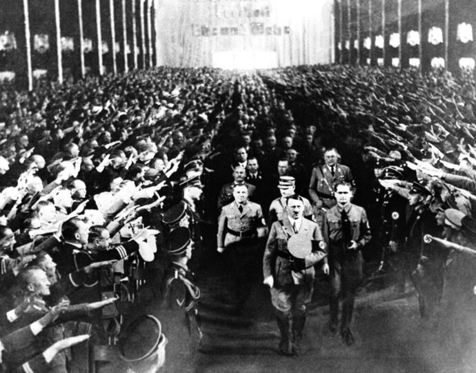 """FILE - This Sept. 11, 1935 file photo shows  Storm Troopers raising their hands in salute as Adolf Hitler leads his staff down the aisle during opening of the National Socialist Party Convention in Nuremberg, Germany.  In March 1933, six years before the war began, Adolf Hitler's storm troopers violently shut down a small German newspaper,  the Munich Post ,  that had devoted close to a decade warning about Hitler's dangers to a free society.  A recent biography published by The Associated Press called, """"Enemy of the People: The Munich Post and the Journalists Who Opposed Hitler"""" by Terrence Petty, captures the early era of Nazi Germany.   (AP Photo)"""
