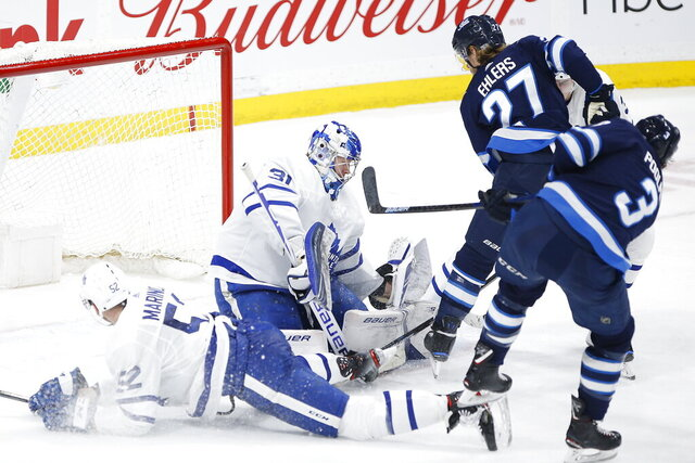 Toronto Maple Leafs goaltender Frederik Andersen (31) saves the shot from Winnipeg Jets' Tucker Poolman (3) during third-period NHL hockey game action in Winnipeg, Manitoba, Thursday, Jan. 2, 2020. (John Woods/The Canadian Press via AP)